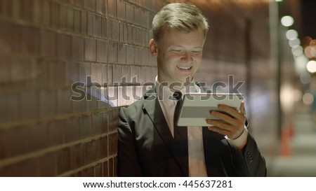 caucasian businessman standing on street in the city at night using digital tablet computer screen excited about positive business news. urban people lifestyle background.  - stock photo