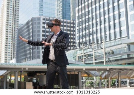 Caucasian Businessman wearing black suit and Virtual Reality Headset (VR) imagine to fighting in the air