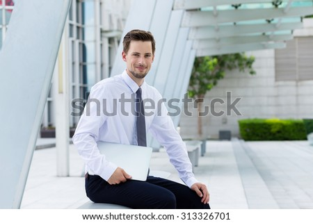 Caucasian businessman with laptop computer and sitting outside