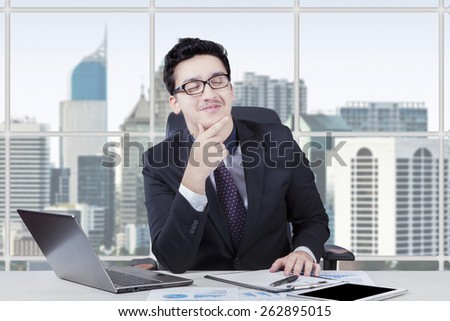 Caucasian businessperson wearing formal suit and sitting in the office while thinking something - stock photo