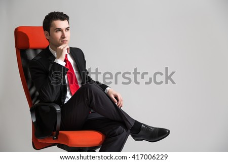 Caucasian businessperson with hand at chin sitting on red swivel chair on grey background - stock photo