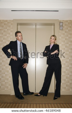 Caucasian businesswoman and businessman stand impatiently as they wait for an elevator. Vertical shot.