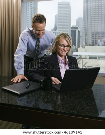 Caucasian businesswoman and middle-aged businessman smile as they look over a laptop computer. The city can be seen through the window in the background. Vertical shot. - stock photo