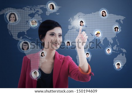 Caucasian businesswoman clicking on the social network map over a blue digital world map - stock photo