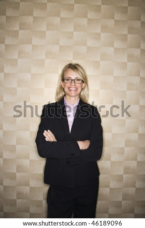 Caucasian businesswoman crosses her arms and smiles towards the camera. Vertical shot. - stock photo