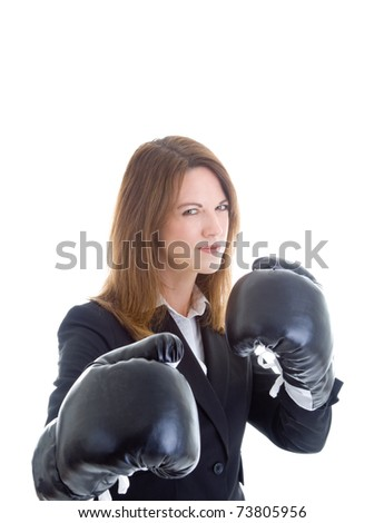 Caucasian businesswoman in a suit wearing boxing gloves, ready for a fight.  She's glaring at the camera.  Isolated on white background. - stock photo