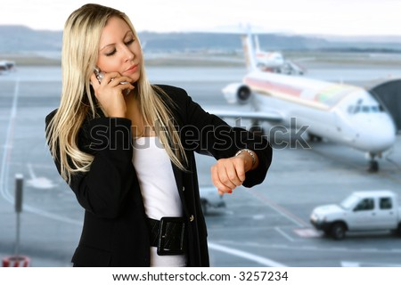 Caucasian businesswoman looking at her watch,  in the departure hall of an airport, waiting to catch her flight for her business travel. Concept of business air travel and time pressure. - stock photo