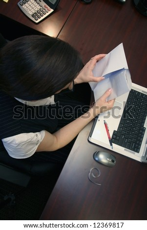 Caucasian businesswoman paying bills while seated at her desk - stock photo