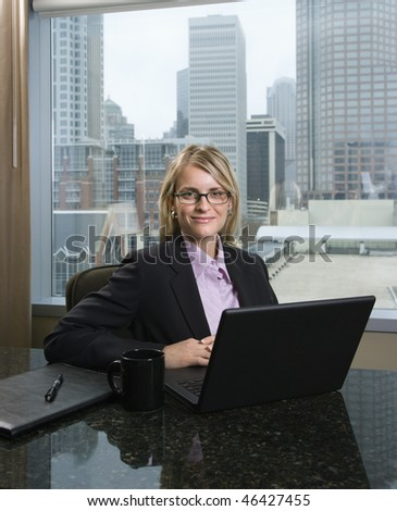 Caucasian businesswoman smiles at the camera while sitting at her laptop. The city can be seen through the window in the background. Vertical shot. - stock photo