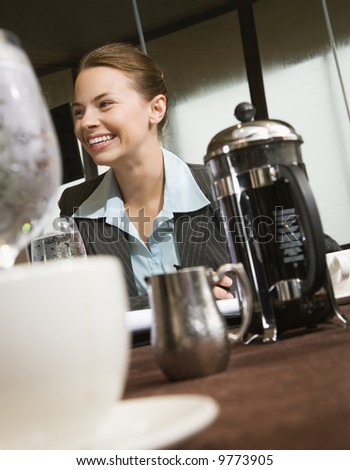 Caucasian businesswoman smiling at table with coffee and beverages.