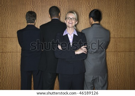 Caucasian businesswoman stands smiling as businessmen stand with their backs turned. Horizontal shot. - stock photo