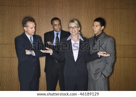 Caucasian businesswoman stands smiling with her hands out as businessmen look at her disapprovingly. Horizontal shot. - stock photo
