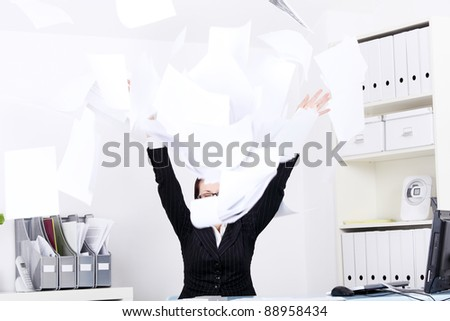 Caucasian businesswoman throwing sheets of paper in the office. - stock photo