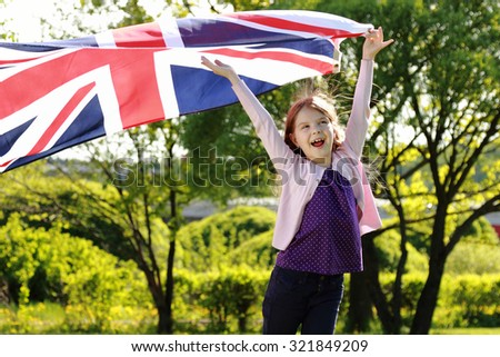 Caucasian cheerful cute girl standing in a park holding a big Britain flag outdoors - stock photo