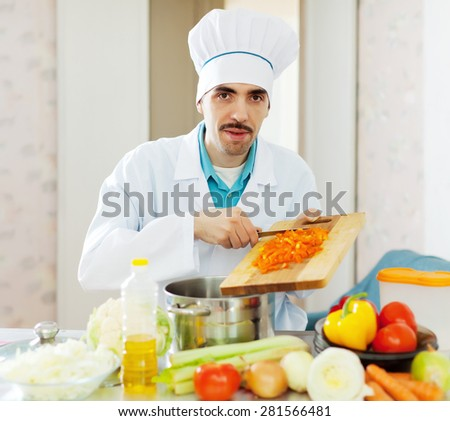 caucasian chef in toque works with vegetables at kitchen - stock photo