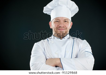 Caucasian chef in uniform with his arms crossed smiling and looking at camera