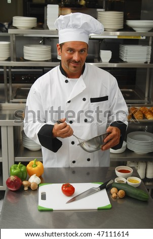 Caucasian chef mixing something in a bowl with fresh vegetables on a cutting board in front of him in a restaurant kitchen. - stock photo