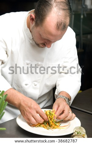 Caucasian chef putting food on a plate in a restaurant kitchen. - stock photo