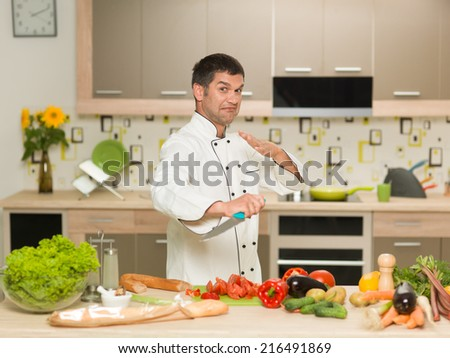 caucasian chef, standing in front of kitchen table with vegetables, holding knife, fighter gesture - stock photo