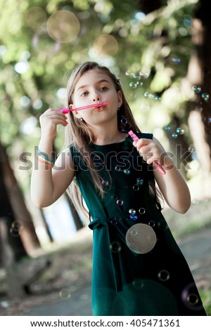 Caucasian child girl blowing soap bubbles outdoor - stock photo