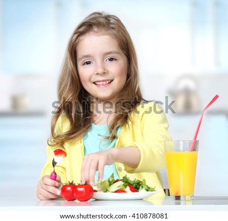 Caucasian child girl eating fresh salad tomatoes drinking orange juice indoors sitting at  kitchen table.Kid healthy food nutrition concept. - stock photo