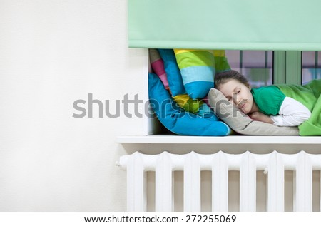 Caucasian child sleeping in clothes on the windowsill, copyspace - stock photo