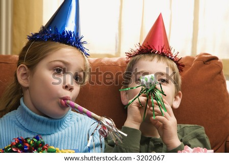 Caucasian children looking bored wearing party hats and blowing noisemakers. - stock photo