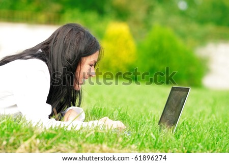 Caucasian college student lying down on the grass working on laptop at campus and laughing. Sunny day.