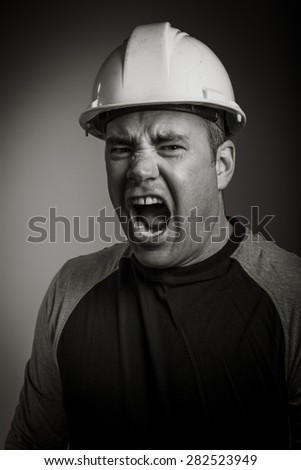 Caucasian contractor male 40 years old shot in studio isolated on grey background, black and white image