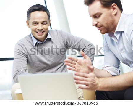 caucasian corporate executive looking at camera and smiling while discussing business with colleague.