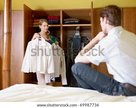 caucasian couple getting dressed in the morning, with woman choosing shirt. Horizontal shape, front view, three quarter length - stock photo