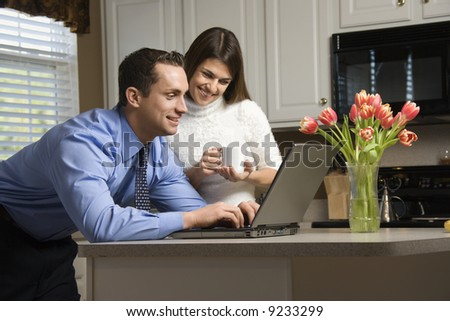 Caucasian couple in kitchen with coffee looking at laptop computer. - stock photo