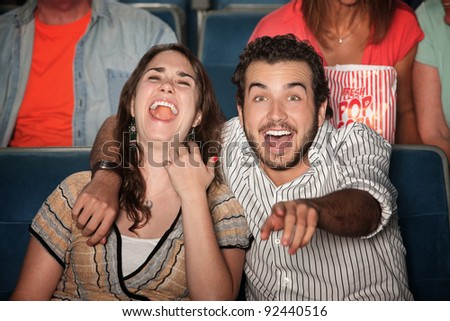 Caucasian couple laugh out loud in theater - stock photo