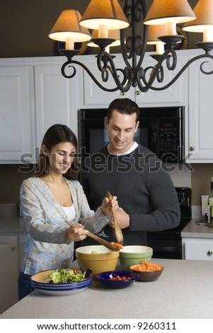 Caucasian couple making salad at kitchen counter. - stock photo