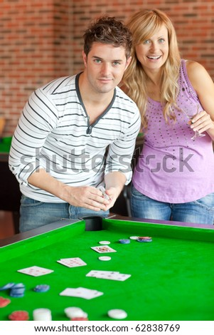 Caucasian couple playing cards on a billiard in a snooker club - stock photo
