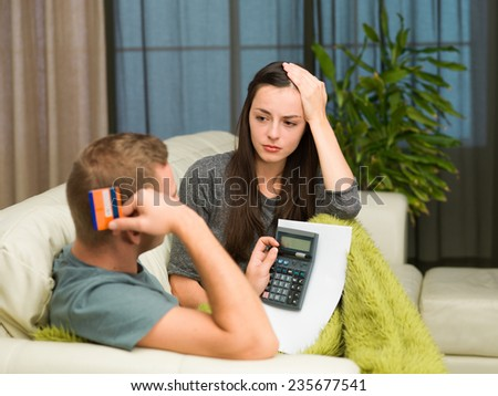 caucasian couple sitting on couch at home calculating expenses - stock photo