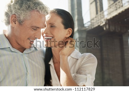 Caucasian couple smiling with bridge in the background - stock photo