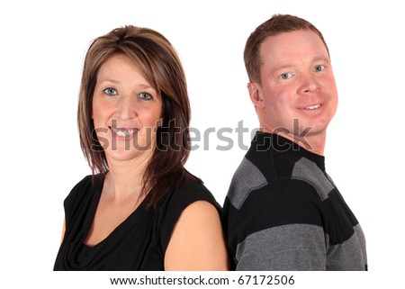 Caucasian couple standing back to back and smiling on a white background