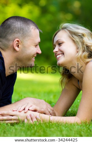 Caucasian couple together on meadow at a summer day - stock photo