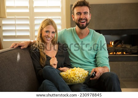 Caucasian couple watching television in the living room
