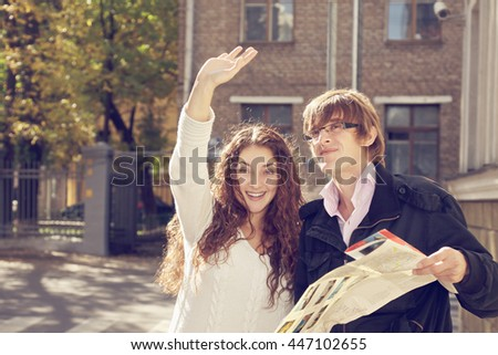 Caucasian couple with city map catching taxi. Toned photo