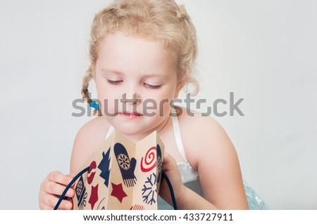 caucasian curly blond surprised girl in a ball gown in the New Year with Christmas snowflakes Christmas gift bags of brown paper on isolated white background studio - stock photo