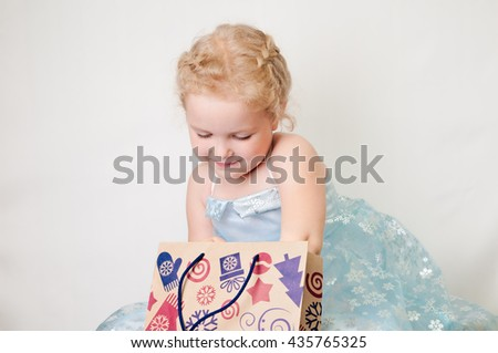 caucasian curly blond surprised girl in a ball gown in the New Year with Christmas snowflakes gift bags of brown paper in a pattern mittens tree gifts in hands on isolate - stock photo
