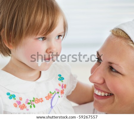 Caucasian cute girl brushing her teeth with her mother in the bathroom - stock photo