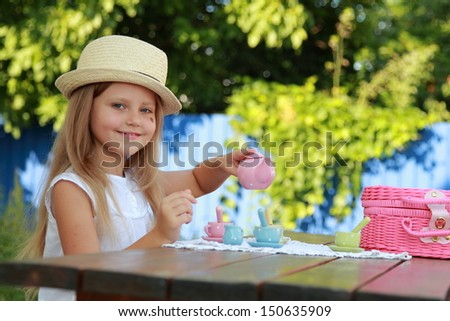 Caucasian cute little girl in a summer hat playing with toys and smiling outdoors