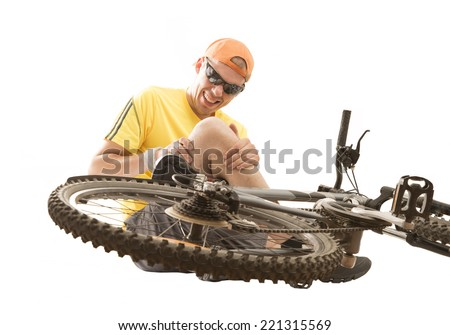 Caucasian cyclist fell down from bike with injured knee joint, painful facial expression and sitting on floor, isolated on white background. - stock photo