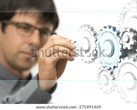 Caucasian engineer drawing gears on a transparent wall. Engineering background concept over white. - stock photo