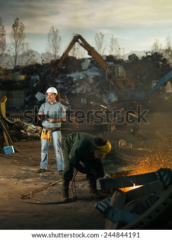 caucasian engineer standing at scrap metal recycling site, inspecting work - stock photo