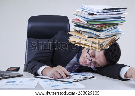 Caucasian entrepreneur sleeping on the tablet with a pile of paperwork on his head - stock photo
