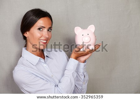 Caucasian ethnicity lady showing piggy bank for savings money while looking at camera on grey texture background